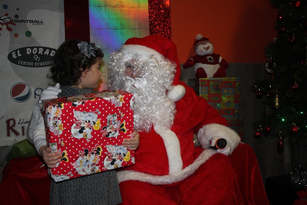 Papa Noel escuchando las peticiones de unas de las niñas asistentes a la Fiesta de Navidad